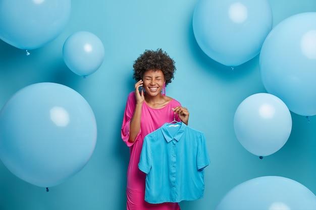 Kleding, mode, stijlconcept. vrolijke donkere vrouw belt vriend via mobiel, houdt modieus shirt op hangers, demonstreert haar stijlvolle garderobe, bereidt zich voor op een speciale gebeurtenis in het leven