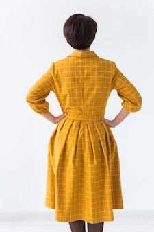Kleding, ontwerper, mensen concept - achteraanzicht van aantrekkelijke vrouw in een gele jurk die zich voordeed op wit
