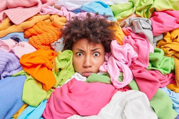 Kleding opruimen. verbaasde geschokte vrouw met krullend haar ruimt kaststokken op van stapel op verschillende veelkleurige kleding, doet snelle zuivering. door de rotzooi sorteren en alles eruit halen