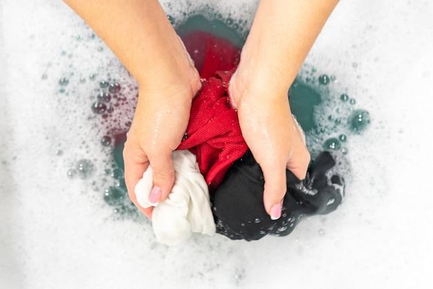 Kleding van verschillende kleuren in een waskom met de hand wassen