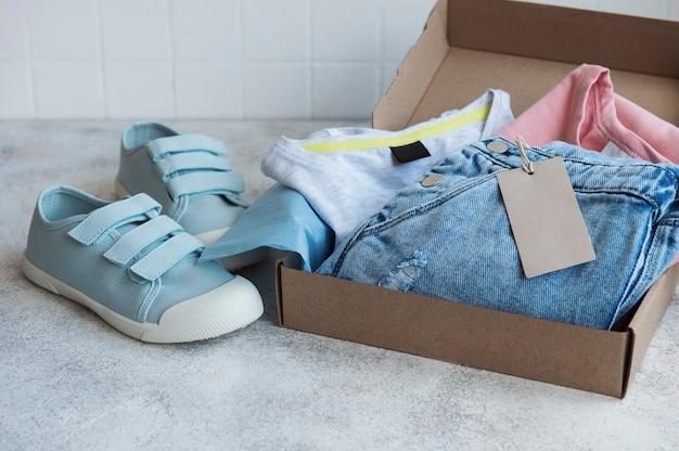 Kleding voor kinderen in een open kartonnen doos. online winkelconcept. levering van kleding.