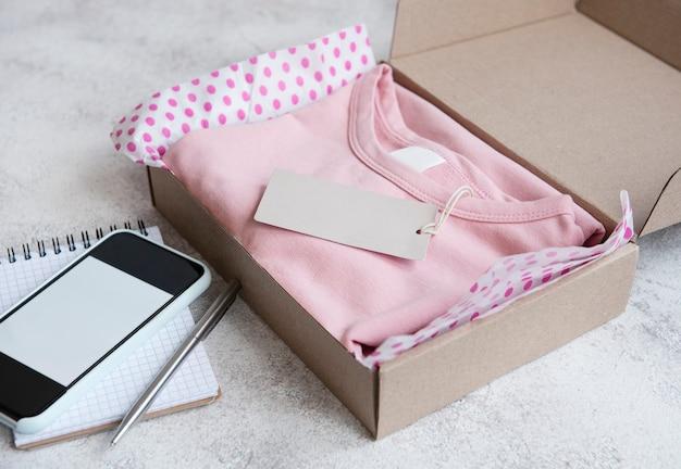 Kleding voor kinderen in een open kartonnen doos. online winkelconcept