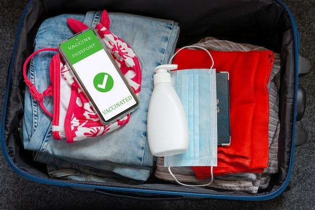 Kleding voor vakantiereizen in de bagagehandtas, beschermend gezichtsmasker, desinfecterende vloeistof in de dispenser en digitale vaccinpaspoortidentificatie in mobiele telefoon. nieuw normaal reisconcept
