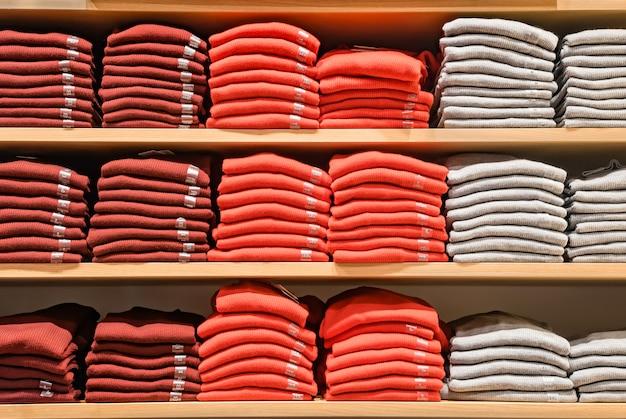 Kleding wordt in de winkel getoond. veel warme truien met felle kleuren worden netjes op een rij op de winkelschappen gestapeld. stapels veelkleurige gebreide wollen kleding. t-shirt op de plank.