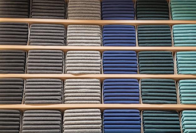 Kleding wordt in de winkel getoond. veel warme truien met verschillende kleuren worden netjes op een rij op de winkelschappen gestapeld. stapels veelkleurige gebreide wollen kleding. t-shirt op de plank
