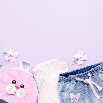 Kledingcollectie voor kleine meisjes plat lag met t-shirt, jeans, rugzak op pastel