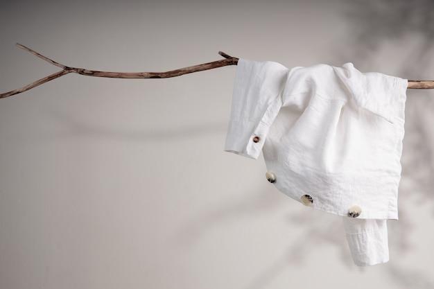 Kledingconcept. witte organische linnen jas hangend aan gedroogde boomtak. schaduwschaduw op de muur