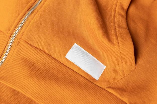 Kledingetiket op oranje sportsweatshirt