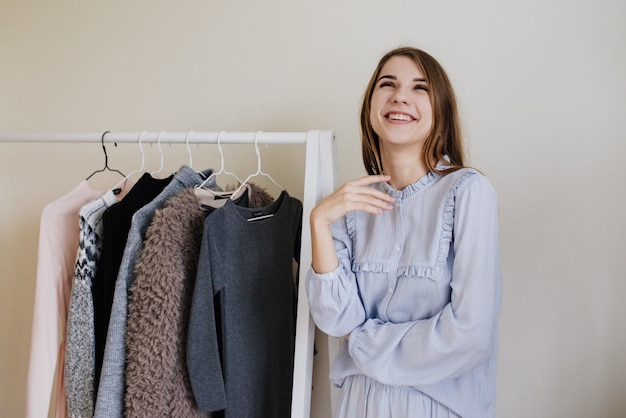 Kledingkast van een jong meisje. jurken op hangers. meel keuze. wat te dragen? een meisje in pyjama weet niet wat ze moet dragen.