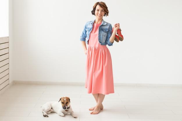Kledingontwerper, mensen, huisdierenconcept - jonge vrouw in kleding en jeansjasje met jack russell