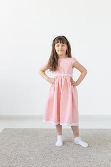 Kledingontwerper, model, mensenconcept - klein meisje is een model, in een roze jurk in de studio
