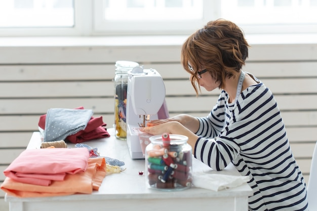 Kledingontwerpster, naaister, mensenconcept - kledingontwerper die in haar atelier werkt