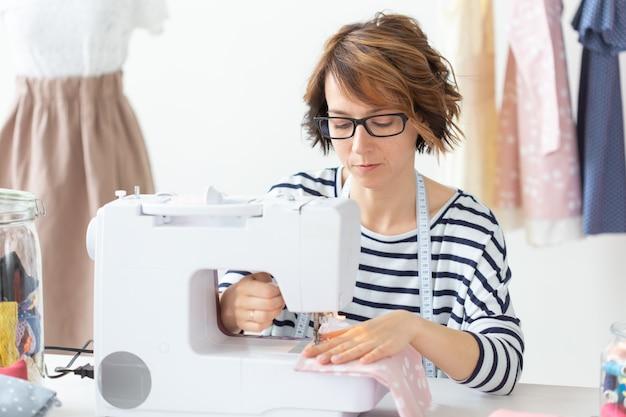 Kledingontwerpster, naaister, mensenconcept - kledingontwerper die in haar atelier werkt.