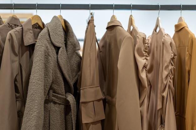 Kledingoverhemden in één kleur hangen hangers op een winkelachtergrond. een verscheidenheid aan kleding hangt in de kledingkast. winkelen seizoen van vakantie te koop