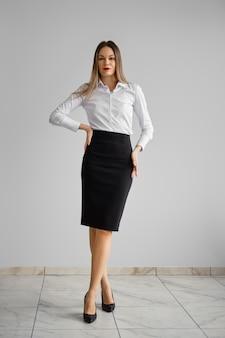 Kledingvoorschrift voor op kantoor - mooi meisje in wit overhemd en strakke zwarte rok