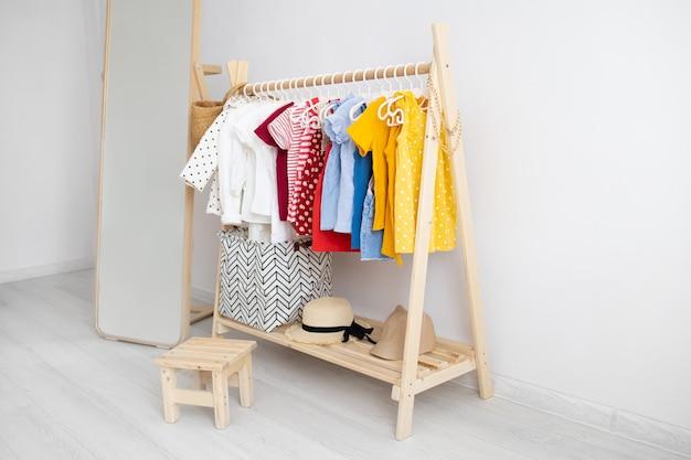 Kleedkast met kleren gerangschikt op kleerhangers