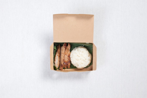 Kleefrijst met gegrild varkensvlees in een doos van bruin papier, op een wit tafelkleed, voedseldoos, thais eten.