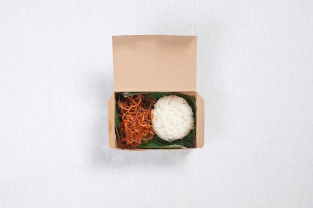 Kleefrijst met gesnipperd varkensvlees in een doos van bruin papier, op een wit tafelkleed, voedseldoos, thais eten.