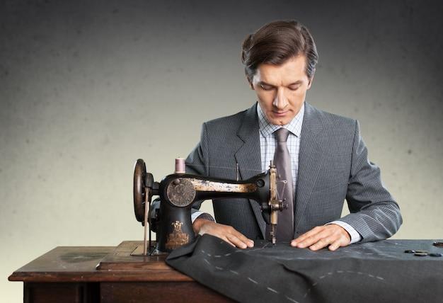 Kleermaker aan het werk. zelfverzekerde jonge kleermaker die kleding naait bij de kleermaker