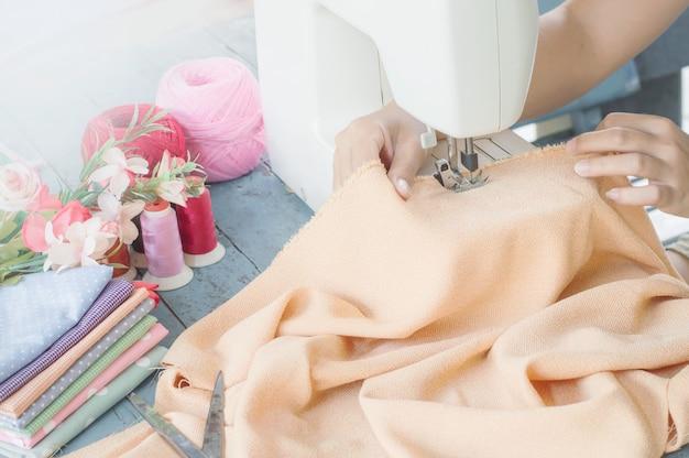 Kleermaker die aan een naaimachine met oranje stof werkt