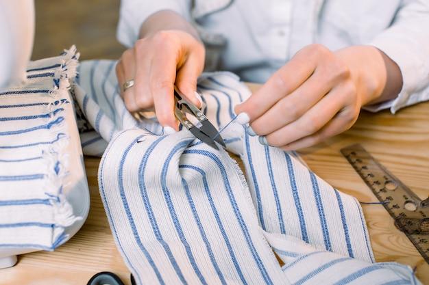 Kleermaker, naaister, modeontwerper concept. vrouwenhanden die met de schaar van de kleermaker en materiële doek werken. detailopname.