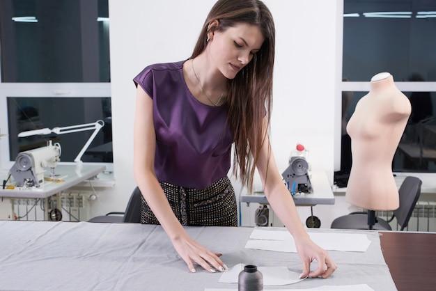 Kleermaker op het werk, lijn tekenen op stof met krijt in atelier studio