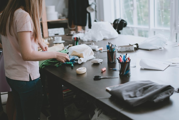 Kleermakers dingen. kleermakersgereedschap. een meisje naait kleren. het meisje maakte het materiaal klaar om kleding te naaien. het proces van werken als kleermaker.