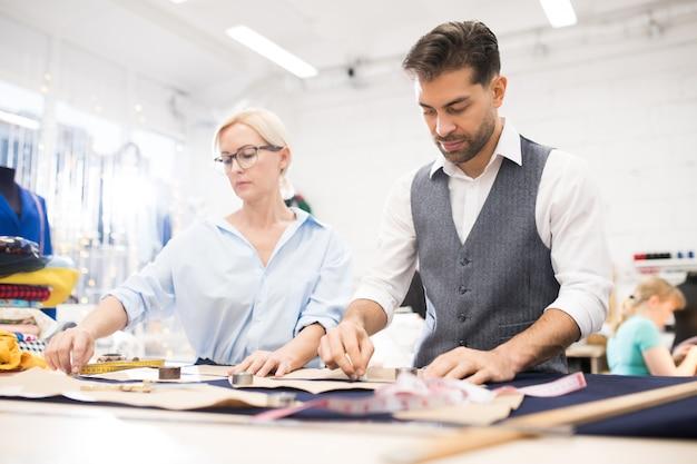 Kleermakers werken aan tafel in atelier studio