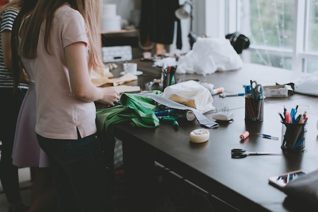 Kleermakersgereedschap. een meisje naait kleren. het meisje maakte het materiaal klaar om kleding te naaien. het proces van werken als kleermaker.
