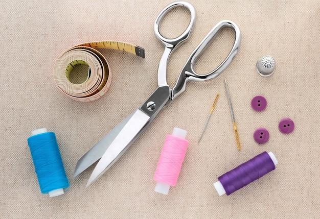 Kleermakersgereedschap: schaar, draad, meetlint, naainaald en vingerhoed.