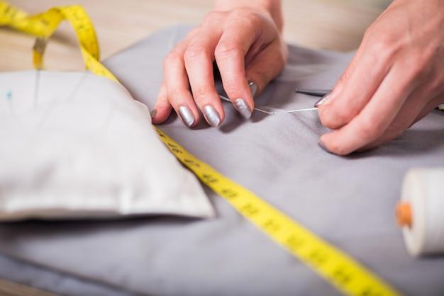 Kleermakershanden die aan nieuwe kleding werken