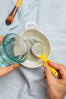 Klei gezichtsmasker voorbereiden. mengen van droge klei met water, bovenaanzicht. huidverzorging concept.
