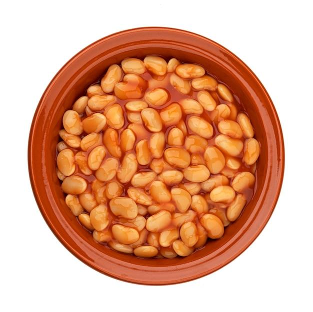 Kleikom gebakken bonen in tomatensaus geïsoleerd op een witte tafel met uitknippad, bovenaanzicht