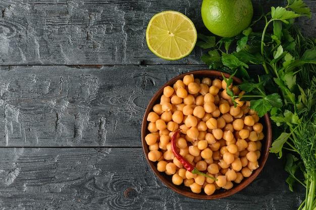 Kleikom gevuld met gekookte kikkererwten op een zwarte houten tafel met peterselie en limoen. vegetarische keuken van peulvruchten. het uitzicht vanaf de top. plat leggen.