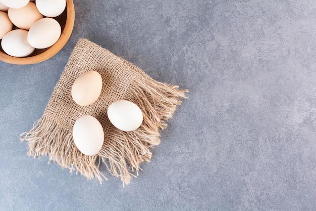 Kleikom vol biologische eieren op stenen tafel.