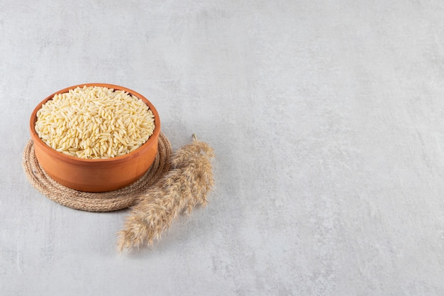 Kleikom vol rauwe rijst die op stenen achtergrond wordt geplaatst.