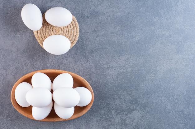 Kleikom vol rauwe witte eieren op stenen tafel.
