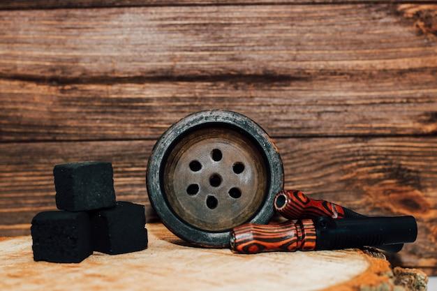 Kleikom voor waterpijp met kokoskolen, houten mondstukken staat op een houten ondergrond.