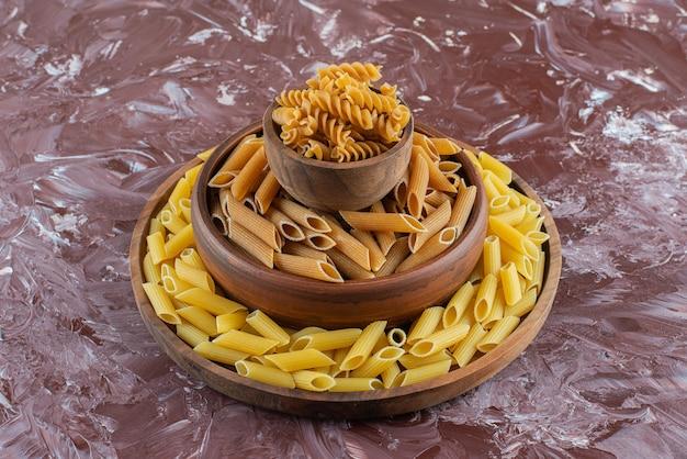 Kleikommen van ruwe penne en fusilli pasta op marmeren oppervlak.