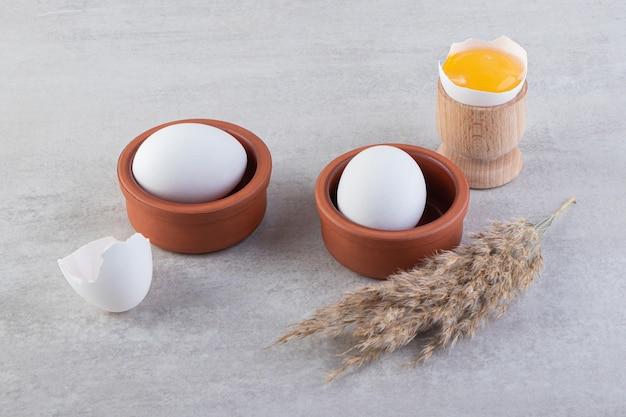 Kleikommen van witte rauwe eieren met eigeel op stenen tafel.