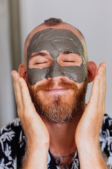 Kleimasker op het gezicht van de jonge knappe man in schoonheidskliniek