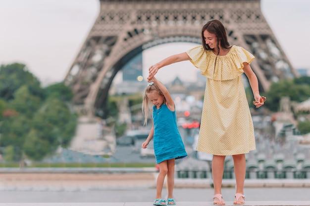 Klein aanbiddelijk meisje en haar jong mamma in parijs dichtbij de toren van eiffel tijdens de zomervakantie