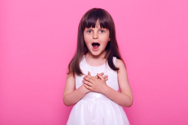 Klein aangenaam verrast meisje kijkt naar voren, onverwachte verrassing, kan haar ogen niet geloven, nam de adem weg van wat ze zag, geïsoleerd over roze muur