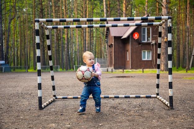 Klein actief meisje baby blond spelen met voetbal bal in het bos rusland