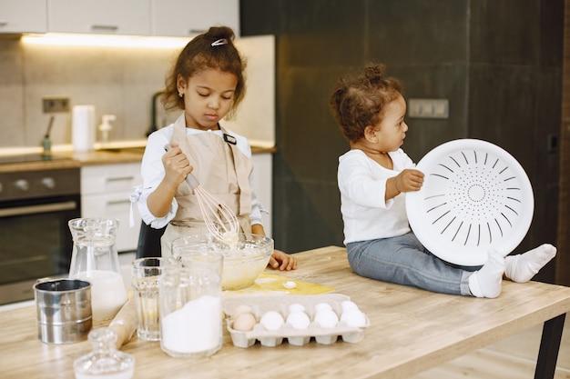 Klein afrikaans-amerikaans meisje dat deeg in een glazen kom mengt en een cake bereidt. haar zus peuter zittend op een tafel.
