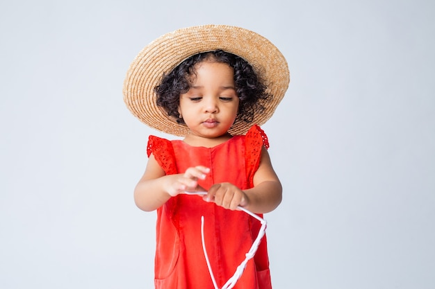 Klein afrikaans amerikaans meisje in rode zomer kleding en een strooien hoed op een witte achtergrond in de studio