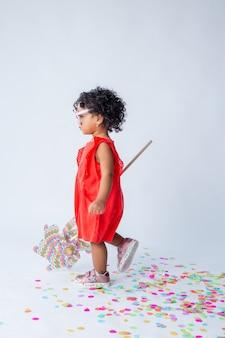Klein afrikaans amerikaans meisje in rode zomerkleren op een witte achtergrond in de studio