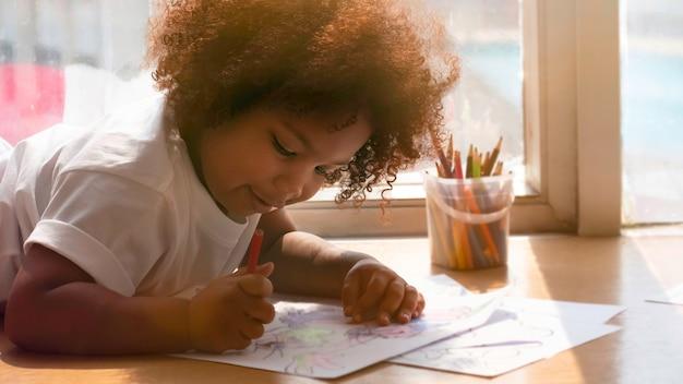 Klein afrikaans meisje dat en met geluk schildert trekt.
