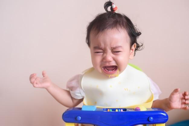 Klein aziatisch babymeisje dat huilt met tranen op haar gezicht tijdens de eettijd, verdriet en ongelukkig, baby-uitdrukkingsconcept