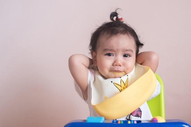 Klein aziatisch babymeisje ongelukkig gezicht in eettijd, verdriet, baby-uitdrukkingsconcept